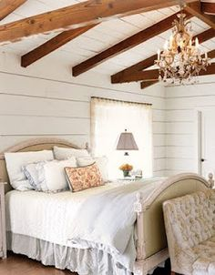 I love the layers of texture...beams, wood slat wall, layers of pillows and love the light!