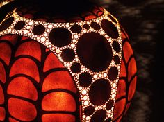 Gourd Lamps by Calabarte. Each gourd lamp is made from a gourd brought from Senegal and their exotic design is achieved after carefully selecting dried shells of gourd fruit and drilling patterns into them. Different patterns are designed by carving deeper or shallower into layers of wood. This allows light to pass through each carving, creating beautiful patterns of light on the walls.