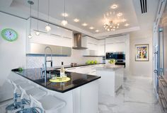 Contemporary white kitchen with marble flooring and white bar stools. Kitchen with sputnik chandelier over kitchen island with marble countertop