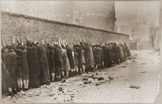 "Jews captured by the SS during the suppression of the Warsaw Ghetto Uprising are lined up against a wall prior to being searched for weapons. The original German caption reads: ""Before the search."""
