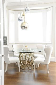 Youngsters Area Home Furnishings Gorgeous Dining Room Features Staggered Brass, Glass, And Chrome Pendants Above A Round Glass Top Dining Table Surround By White Wingback Dining Chairs With Nailhead Trim. Glass Round Dining Table, Glass Dining Room Table, Dining Table Design, Dining Chairs, Small Dining, Round Tables, Small Tables, Glass Room, Glass Tables