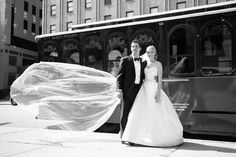 As the newlyweds exit the trolley, the bride's cathedral-length veil blows in the wind. The bride and groom trekked from their gorgeous cathedral ceremony space to the Omni William Penn in a vintage style Trolley courtesy of Molly's Trolleys, which added a unique, urban flair to their classically elegant wedding. In just a few hours they would be dancing their hearts out to knockout songs performed by Pittsburgh's top wedding entertainers. http://www.jpband.com/weddings/