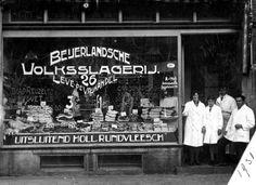 """1931Beijerlandsche Volkslagerij, Toon van 't Hoff Beijerlandschelaan 26RotterdamDe foto is genomen bij de opening van de 3e slagerij van slager Anthonij van 't Hoff. Op het winkelraam staat de slagzin: """"Leve de vrijhandel."""" De Rotterdamse slager-ondernemer heeft hem waarschijnlijk, uit protest, laten plaatsen als gevolg van de crisis op de Amerikaanse effectenbeurzen in 1929 waardoor wereldwijd protectionistische maatregelen genomen werden om de eigen markten te beschermen."""