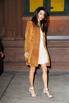 Amal Clooney in a suede jacket, white dress, and white heels