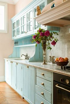 aqua/ turquoise kitchen cabinets, lightly glazed to look antique or distressed. Love that they have bead-board type fronts too... wish I could see them from the front. Marble backsplash and counter is gorgeous.
