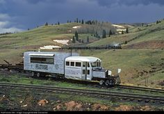 """As a spring storm brews to the west, Rio Grande Southern Galloping Goose No. 5 is meeting the regular Cumbres and Toltec Scenic Railroad passenger train at Osier, Colorado, on May 25, 1999. This """"motor"""" as RGS originally called them, was the brainchild of the creative workers at the RGS' Ridgway Shops, to provide a less expensive way to operate trains on an expensive-to-operate narrow gauge mountain railroad."""