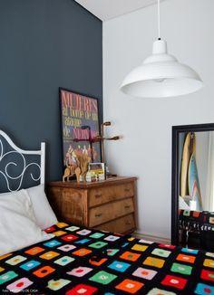 Quarto de hóspedes tem parede cinza, cama de ferro vintage e colcha de crochet.