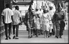 Two young black men pass Ku Klux Klan marchers in downtown Salisbury, August 1964.