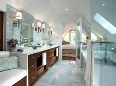 beautiful spa like master bathroom design with light blue gray walls paint color, blue mosaic linear glass tiles backsplash, zebra wood modern bathroom vabinet vanity, glass vessel sinks, double sinks, polished nickel modern sconces, wall mount faucets, built-in bench, gray damask pillows and frameless glass shower..