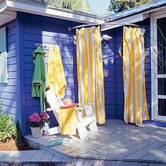 Cheerful yellow-striped curtains hang from an outdoor shower built into the corner of a deck – cute and simple.