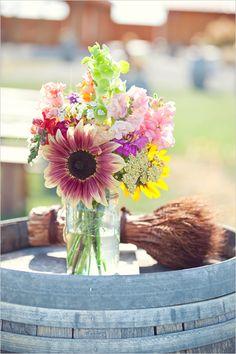 Bundled wheat and bold flowers in mason jar atop vintage wine barrel.