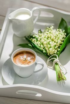 White tray. Coffee .Cream for it.And delicate lilies-in-the-valley.Lovely combination.