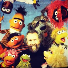 Jim Henson, surrounding by his felt children from The Muppet Show, Sesame Street and Fraggle Rock.
