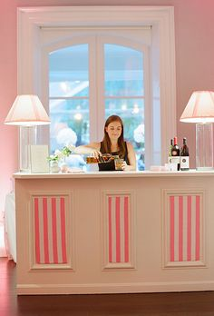 Bartenders served custom libations from white bars outfitted with striped pink panels (Photo: Kate Headley)