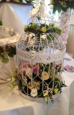 Birdcage arrangement. For weddings or garden parties. Filled with White Roses, Pink and White Lisianthus, Lilac, Vintage Roses and Eucalyptus. The outside of the cage has also been decorated in Trailing Ivy and Spray Roses.