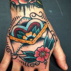 Traitional tattoos. Hand tattoo. Envelope and flower tattoo.
