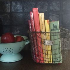 arrange your cookbooks in a cute vintage basket and keep them in arms reach on your kitchen counter. old cookbooks have the best recipes and their worn covers are perfect.