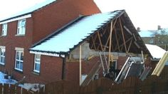 External wall of a house collapses due to snow loading on poorly supported car port.