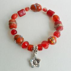Handmade Jewellery - Bracelet £5.00. A gift idea by Braceletsetc By Wendy found on www.MyOwnCreation.co.uk: Made with a mix of pretty light red glass beads, silver plated flower spacers and flower pendant, approx 7.5 inches.  Includes organza gift bag.