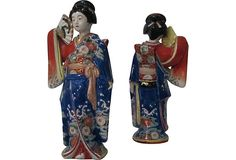 Pair of lavishly decorated Japanese Geishas, solid ceramic in a range of blues, cinnabar, gold, white, black, and green. Although a pair, the subtle difference is in the tilt of one of the Geisha's heads and the face of one is fuller than that of the other.