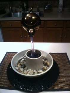 Use a table top water fountain without pump for counter centerpiece......add stones..etc...