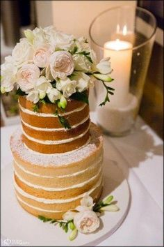 Now trending:  Naked wedding cakes......Naked Cake Topped with White Flowers, Next to Candle