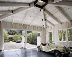 Garage with high white washed ceilings and doors that open outward.