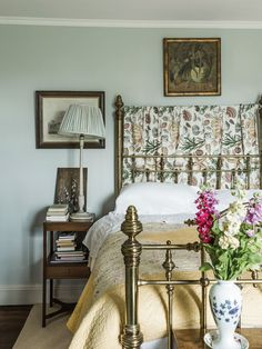 In the guest room, a painted-wood lamp with a textile shade next to a brass bed covered with a Welsh quilt. (Photo: Martin Morrell)