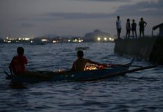 Typhoon survivors paddle out to sea to float flowers at a coastal village in Tacloban city, Leyte province in central Philippines Saturday, Nov. 8, 2014 to commemorate the moment when Haiyan barreled inland from the Pacific with ferocious winds and tsunami-like waves, leaving more than 7,300 dead or missing and leveling entire villages in the world's deadliest disaster last year. (AP Photo/Bullit Marquez)