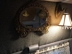 """Antique gilded cast iron """"cherubs"""" mirror with beveled glass, and a Re-Store salvage light wired to run off of a power converter."""