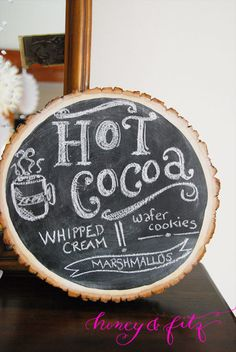 winter birthday party by Honey & Fitz: hot cocoa bar sign on a wood slice painted with chalkboard paint