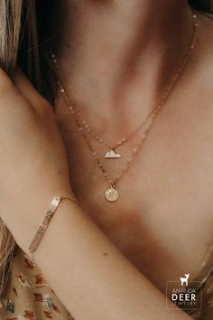 Got wanderlust? Us too! This layered necklace set is the cutest! Our little gold mountain and compass necklaces pair so well together. Shop all our pieces on amandadeer.com #layerednecklace #wanderlust #daintyjewelry