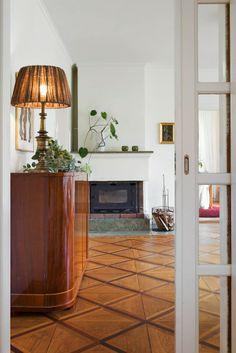 Vackra detaljer, till vardagsrummet en skjutdörr med glas och i bakgrunden den murade öppna spisen
