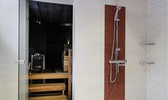 Kylpyhuone ja sauna, n. 7,5 m². Valkoista pesuhuonetta on piristetty ihastuttavilla, punaisilla mosaiikkitehosteilla. Tunnelmallinen sauna on luotu kauniilla materiaaleilla ja sopivalla valaistuksella. Tässä saunassa saunomiselämys on todella rentouttava!