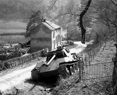 A abandoned Panther Ausf G sitting on a narrow country road likely ran out of fuel during it's retreat back toward Germany in 1945