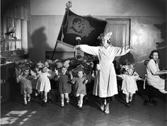 non-trot tots wearing butterfly bows (both girlz & boyz) dancing in front of Lenin-Stalin flag. photo by Margaret Bourke-White, 1941