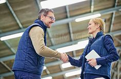 Shot of two people shaking hands in a large warehouse - stock photo #1184070