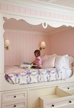 The pale pink and cream beadboard of the alcove enclose the bed in classic lines and feminine colors. Folding sconces promise optimal reading light, and the blue-and-pink patterned quilt adds sweetness. The Swedish-inspired built-in bed has a glide mechanism (brainchild of builder Jeff Ford) that allows the mattress to be easily pulled out to be made. Steps cleverly disguised as drawers add to the magic of this room.