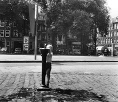 1950's. A child drinks water from a water fountain at the Haarlemmerplein in Amsterdam. #amsterdam #1950 #Haarlemmerplein