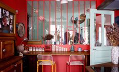 Red kitchen with a glass wall and bar table in a colourful Paris apartment