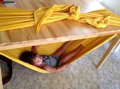 Create a kid-sized hammock with some fabric and a table.Source: Joyful Abode Use a woven babywearing wrap (not a blanket) for this one.