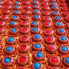 Perfect football snack. Melt Hershey kisses onto waffle pretzels for 2 min in the oven at 350 - then press m&ms into each one. Cool in the fridge. I used red an blue for our favorite team. Go Pats!!!  Also great for kids to get involved with.