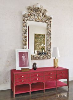 de la Torre designed a nailhead-trimmed console in red horsehair from John Rosselli & Associates and hung an elaborately baroque-style shell mirror acquired from Drake.