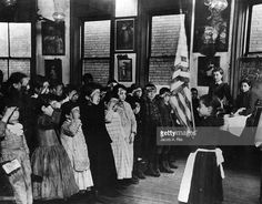 Children of Mott Street Industrial School, New York, salute the Stars and Stripes, and repeat the Oath of Allegiance. This photograph is one of a series taken of New York's slums