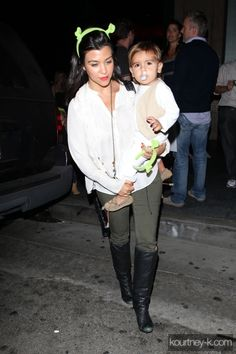 Kourtney Kardashian wearing H&M Lace Waistcoat K-DASH by Kardashian Stretch Blouse With Back Button Detail Balenciaga Black Arena Classic Square Bag Maison Martin Margiela Tall Knee-High Boots Henry and Belle olive skinny jeans