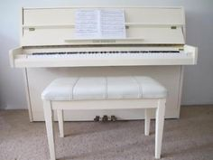 upright piano in ivory just like ours.... love the padded bench seat cover