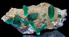 Brilliant green Dioptase crystals set atop blue Shattuckite covered matrix! This is a specimen that is both visually attractive and in excellent condition. The Dioptase crystals are super sharp with a glassy luster.  It is doubly terminated as well. Patches of blue Shattuckite covers the matrix and is further accented by greenish-brown Mottramite. Aesthetic and in excellent condition! From the Omaue Mine,  Namibia. Measures 3.8 cm by 7.5 cm by 2.4 cm  Price $2850