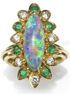 An opal, diamond and emerald ring mounted in eighteen karat gold.