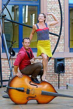 """Cie Du Mirador - Reizvolle Annäherungen zweier sich wiederbegegnender Menschen entwickeln sich mit Musik, Poesie und Spaß. Ein Kontrabass und ein riesiges """"Spinnrad"""" bestimmen den Rhythmus."""