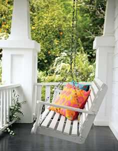 white wooden slat porch swing. white porch. orange, pink, blue pillows. american cottage.